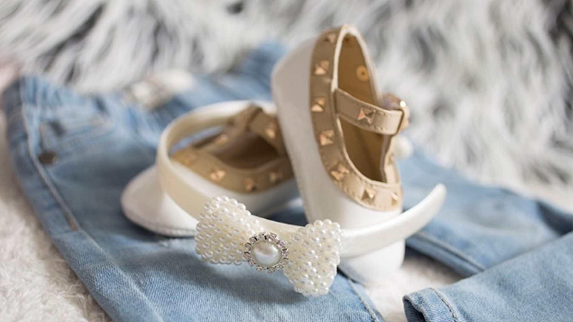 White and gold baby shoes with white beaded Alice band resting on a pair of baby jeans