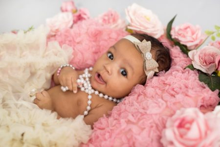 Baby wearing ribbon headband lying on roses