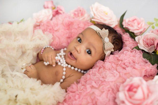 Baby wearing ribbon headband lying on roses
